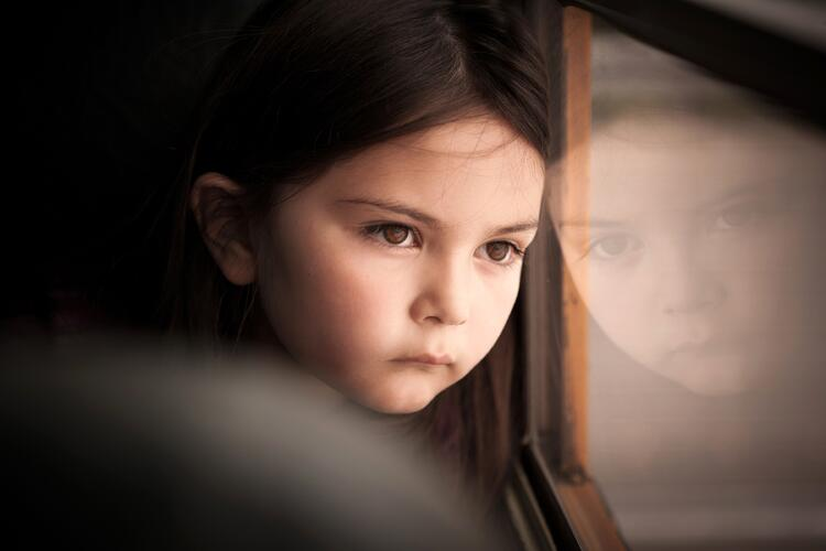 little girl looking out bus window